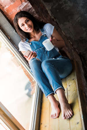 Beautiful Afro American girl in denim overall is using a smart phone, holding a cup and smiling while sitting on the window sill at home Stock Photo