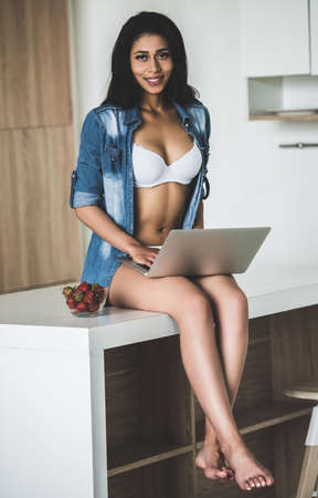 Beautiful Afro American girl in white lingerie and unbuttoned jean shirt is using a laptop and smiling while sitting in kitchen at home Stock Photo