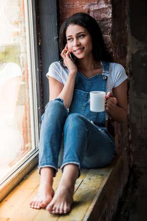Het mooie Amerikaanse meisje van Afro in globaal denim spreekt op de mobiele telefoon, houdt een kop en glimlacht terwijl thuis het zitten op de venstervensterbank