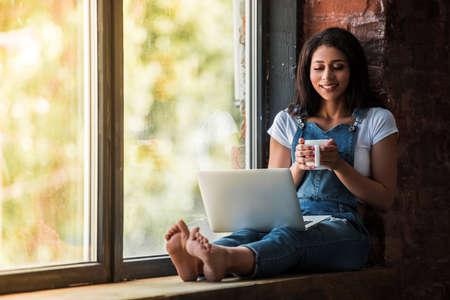 Het mooie Amerikaanse meisje van Afro in globaal denim gebruikt laptop, houdt een kop en glimlacht terwijl thuis het zitten op de venstervensterbank Stockfoto