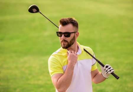 Handsome guy is holding a golf club and looking away while standing on golf course Stock fotó