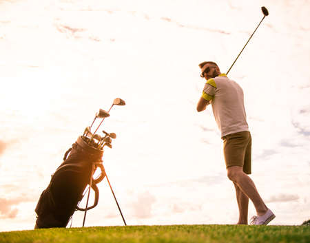 Full length portrait of handsome guy using a golf club while playing golf Фото со стока