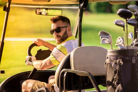 ハンサムな男は、ゴルフカートを運転しながら、カメラを見ています