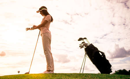 Full length portrait of beautiful young woman holding a golf club while standing on golf course