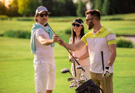 ゴルフ場に立っている間、二人の男と女がゴルフクラブを選んで話して、微笑んでいる 写真素材