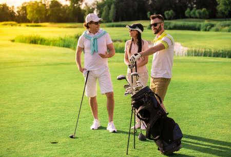2 人の男性と女性がゴルフクラブを選ぶ、話、ゴルフコースに立っている間笑顔 写真素材