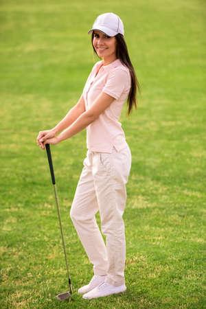 フルレングスゴルフクラブを構えている美しい若い女性の肖像画, ゴルフコースに立っている間、カメラと笑顔を見て 写真素材