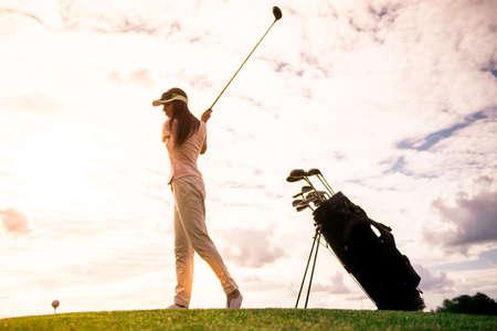 ゴルフをプレイしながら、ゴルフクラブを使用して、美しい若い女性の全長ポートレート 写真素材