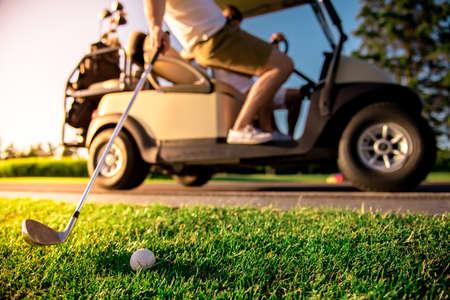 ゴルフカートを運転するハンサムな男性のクロップド画像は、一人の男がボールでゴルフクラブを上げている、焦点でボール 写真素材