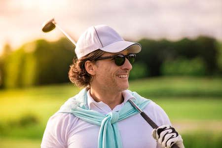 ハンサムな男のゴルフ クラブを握り、よそ見やゴルフコースに立っている間笑顔