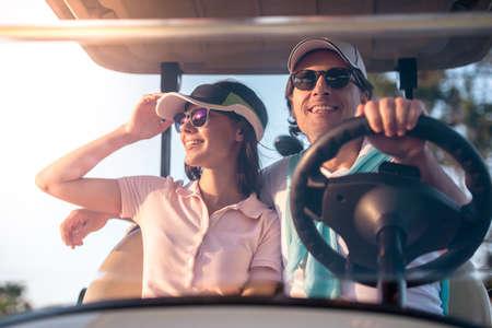 美しいカップルは、ゴルフカートを運転しながら笑顔です