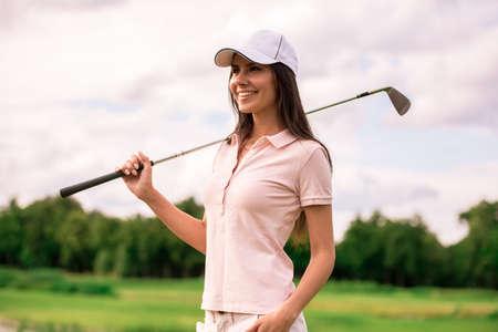 ゴルフ場に立っている間、美しい若い女性がゴルフクラブを構えて微笑んでいる