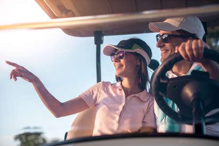 ゴルフカートを運転しながら、美しいカップルが話して、微笑んでいます 写真素材