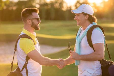 Knappe mannen schudden handen en glimlachen wanneer ze op een golfbaan ontmoeten