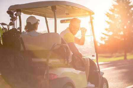 Back view of handsome men driving a golf cart, one guy is looking at camera and smiling