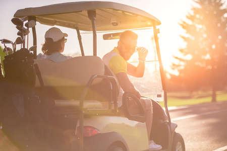 De achtermening van knappe mensen die een golfkar drijven, één kerel bekijkt camera en glimlacht