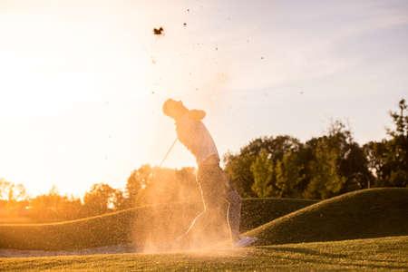 ハンサムな男はゴルフをしながらゴルフクラブを使用しています, 美しい太陽輝く, 砂の飛散