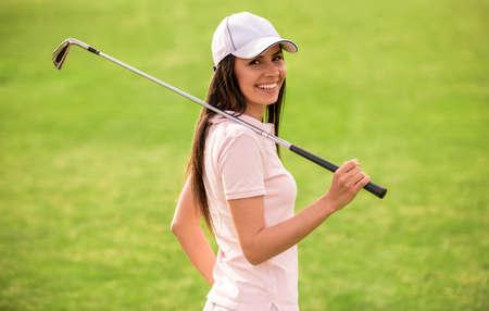 De mooie jonge vrouw houdt een golfclub, bekijkt camera en glimlacht terwijl status op golfcursus