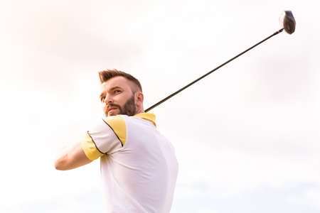 Handsome guy is using a golf club while playing golf