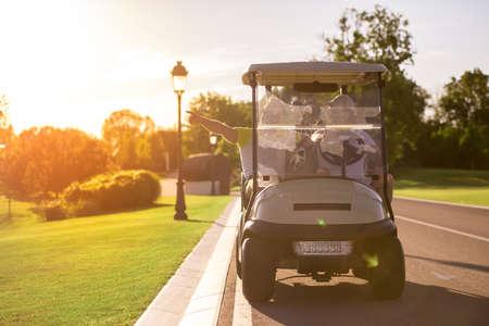 ハンサムな男性は、ゴルフカートを運転し、ゴルフホールを探しています, 美しい日差し 写真素材