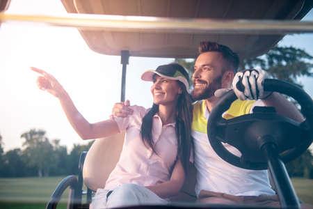 ゴルフカートを運転しながら、美しい若いカップルが話していると笑顔です