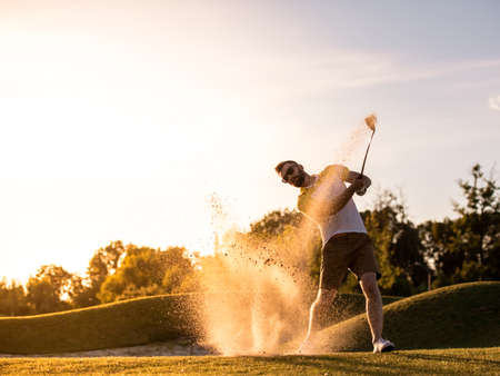 Handsome guy is using a golf club while playing golf, beautiful sun shining, splashed of sand