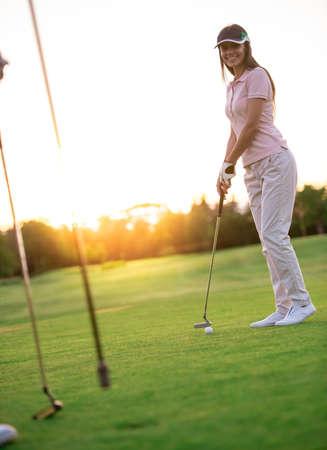 友達と一緒にゴルフをしながら、美しい若い女性が微笑んでいる