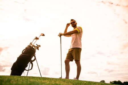 ゴルフクラブを構えてゴルフコースに立っているハンサムな男の全長ポートレート