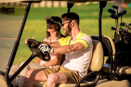 Het mooie paar spreekt en glimlacht terwijl het drijven van een golfkar Stockfoto