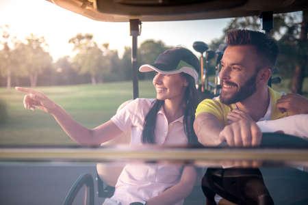 美しい若いカップルが話しているし、ゴルフのカートを運転中笑みを浮かべて