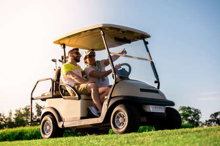 Handsome men are talking and smiling while driving a golf cart and searching for a golf hole