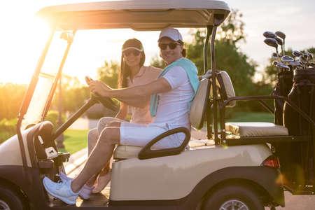 Het mooie paar bekijkt camera en glimlacht terwijl het drijven van een golfkar