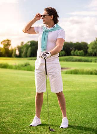 ゴルフクラブを構えているハンサムな男性の全長肖像画は、golf コースに立っている間、離れて微笑んでいます 写真素材