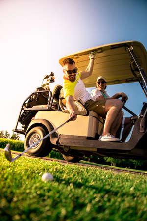 ハンサムな男性は、ゴルフカートを運転しながら微笑んでいる、一人の男は、ボールでゴルフクラブを上げています