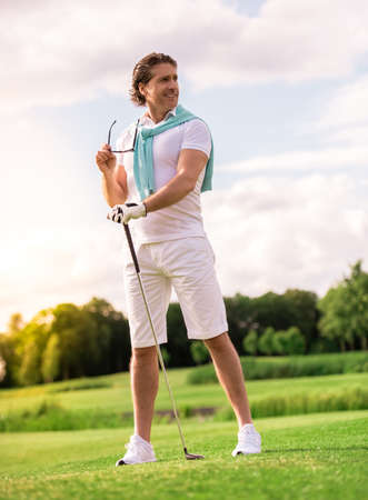 Full length portrait of handsome man holding a golf club, looking away and smiling while standing on golf course