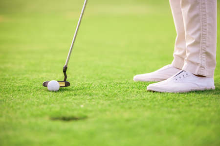 Cropped image of a person playing golf, a golf hole in the foreground