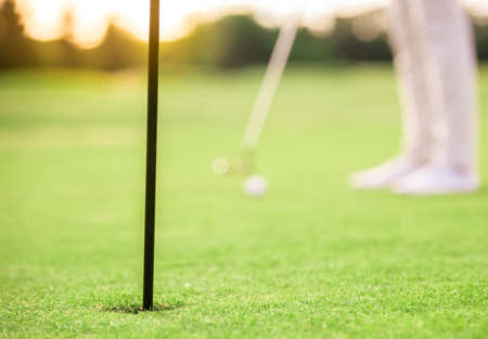 Bijgesneden afbeelding van een persoon die golf speelt, een golfgat op de voorgrond