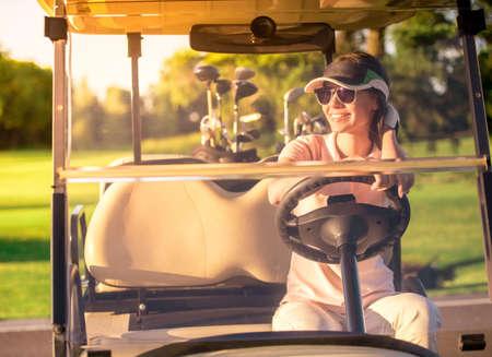 美しい若い女性は、ゴルフカートを運転しながら微笑んでいます 写真素材