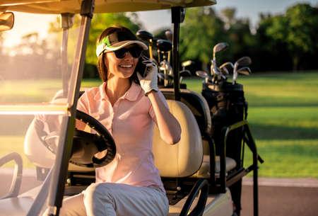 美しい若い女性が携帯電話で話し、ゴルフカートを運転しながら笑っている