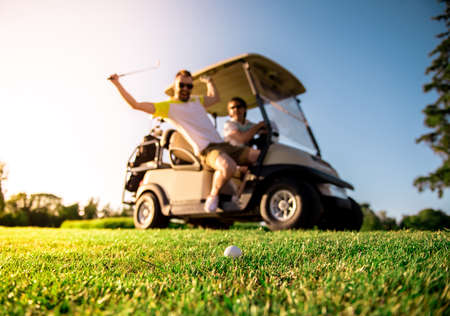 Handsome men are smiling while driving a golf cart, one guy is raising a golf club at the ball, ball in focus