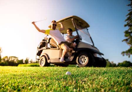 Knappe mannen glimlachen terwijl het besturen van een golfkar, een man is het verhogen van een golfclub op de bal, bal in focus Stockfoto - 85473330