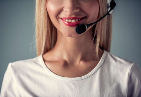Cropped image of beautiful young woman in headset smiling, on gray background