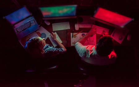 Top view of beautiful young businessman and woman working with computer in office at night