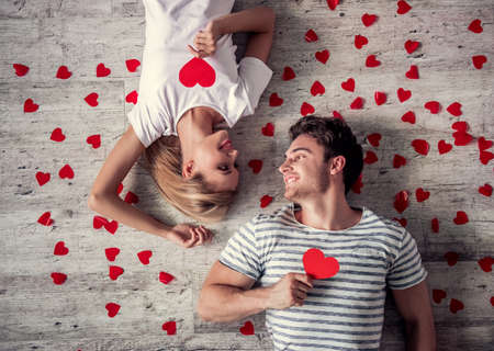 Top view of beautiful young couple holding red paper hearts, looking at each other and smiling while lying on the floor