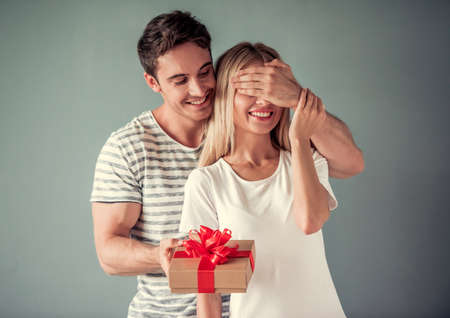 Handsome young man is holding a gift box and covering his girlfriend eyes making a surprise, both are smiling, on gray background Stockfoto