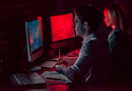 Beautiful young businessman and woman are working with computer in office at night