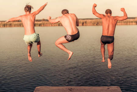 Handsome guys are jumping from pier into the lake, beautiful view Stock Photo