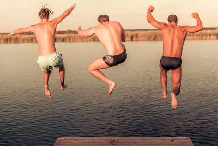 Knappe jongens springen van pier naar het meer, prachtig uitzicht Stockfoto