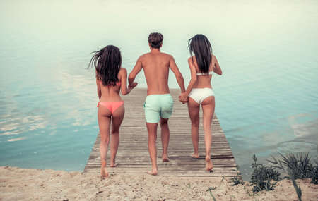Back view of beautiful girls and guy holding hands and running along the pier ready to jump into the water