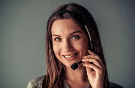 Mooie zakenvrouw in de headset kijkt naar de camera en glimlacht, op een grijze achtergrond